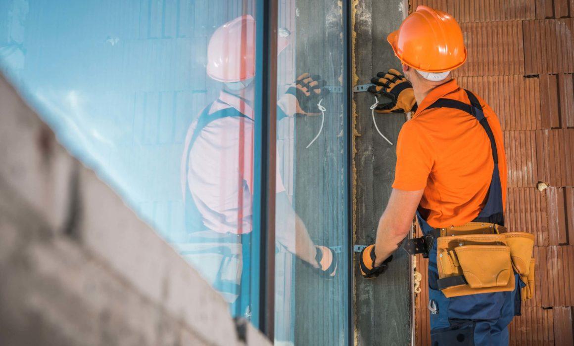 Worker repairs commercial glass window in Rochdale, MA